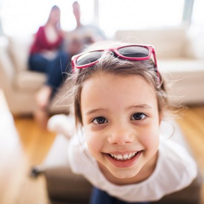 Young happy child with parents in the background packing for holidays.